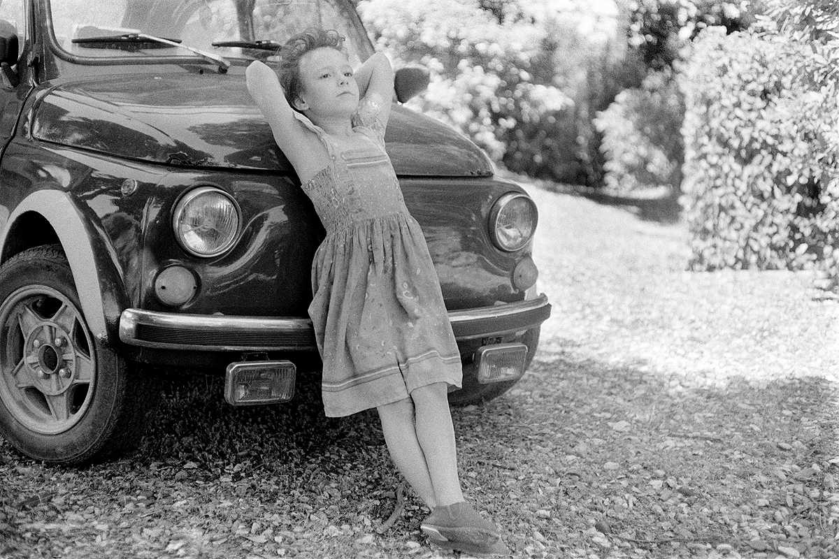 Little girl leans on a Fiat 500. Shot with real film on location in Tuscany, Italy by Fine Art photographer Angela Cappetta