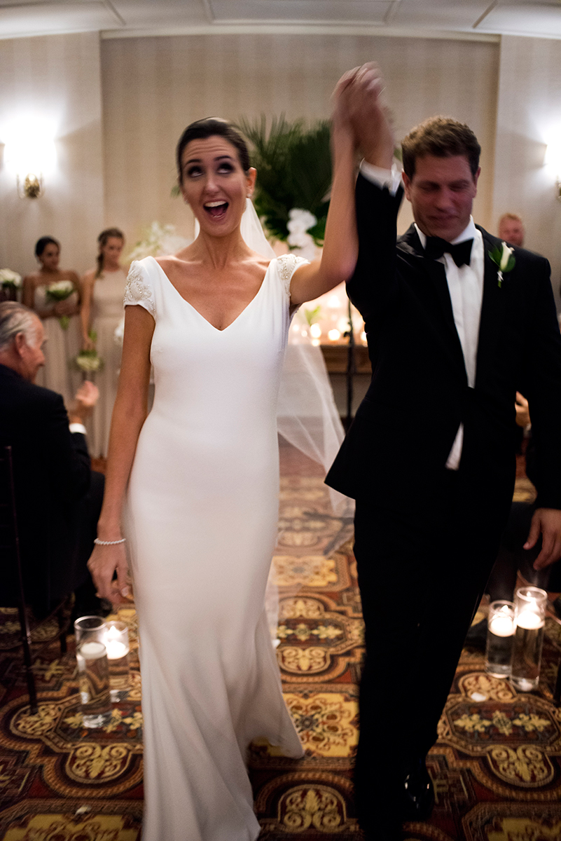 An overjoyed couple recesses their ceremony at the New York Athletic club shot with DSLR by Angela Cappetta fine art wedding photographer.
