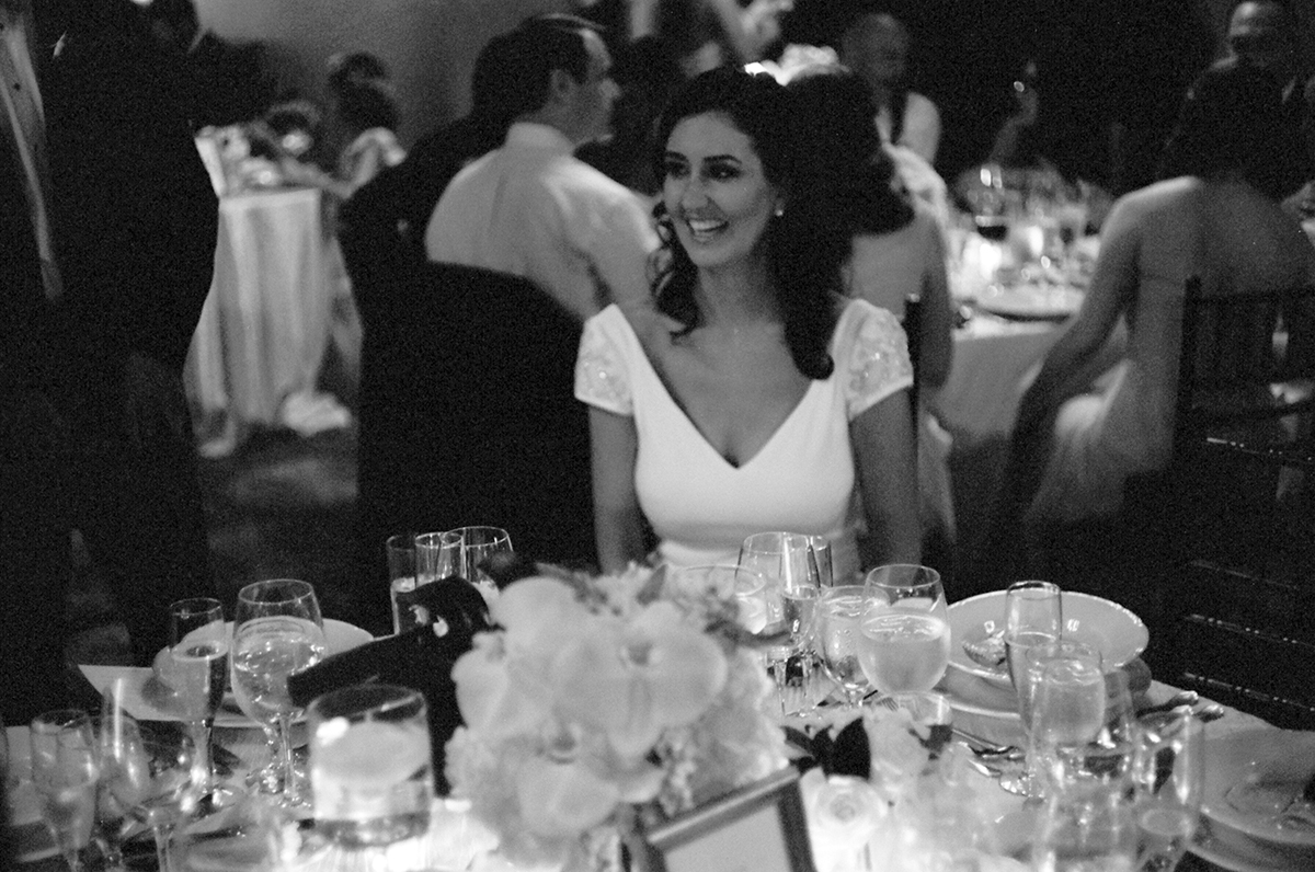 A joyful bride smiles ear to ear at their wedding reception at the New York Athletic club shot with real film by Angela Cappetta fine art wedding photographer.