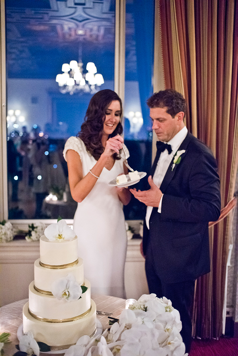 Cutting the wedding cake by Nine Cakes the New York Athletic club shot with DSLR by Angela Cappetta fine art wedding photographer.