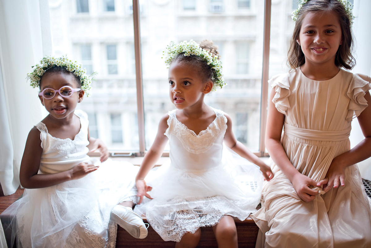 Little flower girls play in a window seat at the New York Athletic club shot with DSLR by Angela Cappetta fine art wedding photographer.