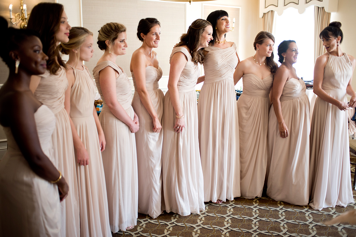Bridesmaids watch Courtney get her veil put on at the New York Athletic club shot with DSLR by Angela Cappetta fine art wedding photographer.