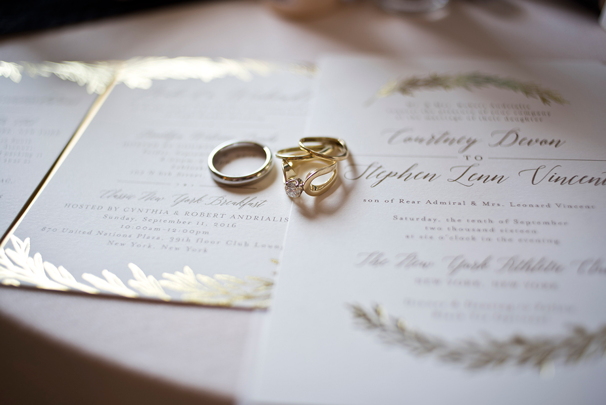 Wedding bands and embossed printing on invitations at the New York Athletic club shot with DSLR by Angela Cappetta fine art wedding photographer.