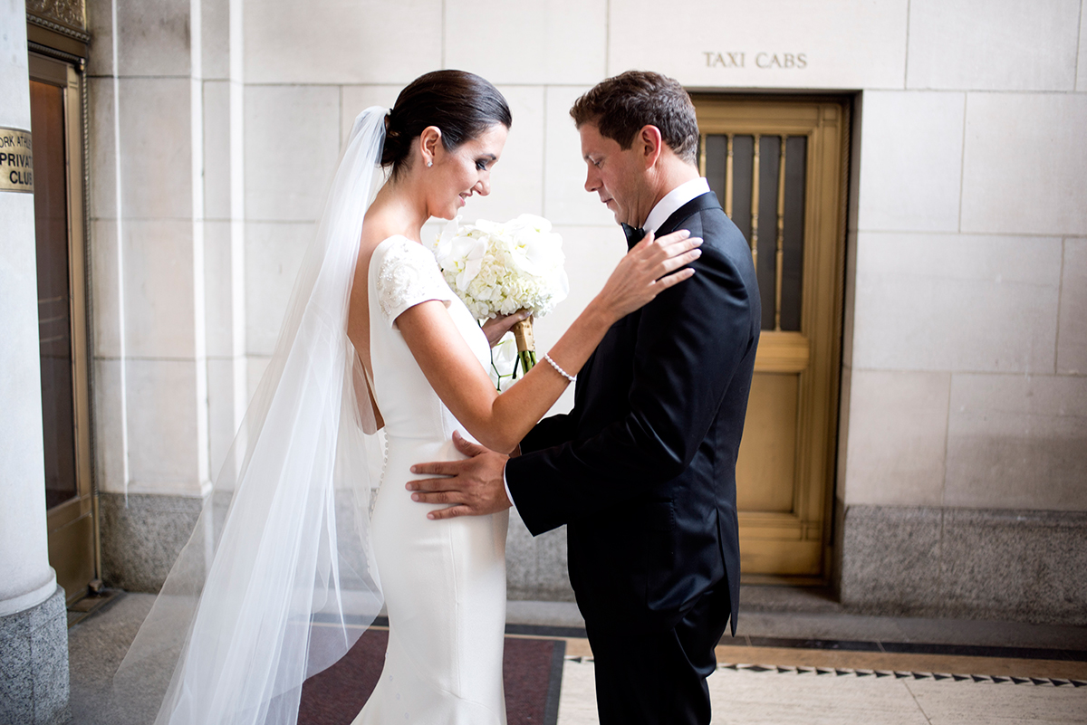 A nervous but joyful couple has their first look on the steps of the New York Athletic club shot with DSLR by Angela Cappetta fine art wedding photographer.