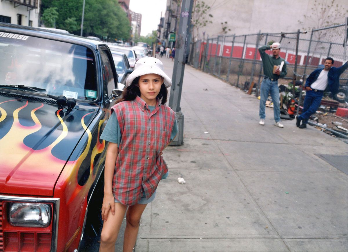 Glendalis, a girl who grew up on the Lower East Side before gentrification, poses beside a truck with flames behind it. Her father and uncle linger in the background. Shot with medium format film by fine art photographer Angela Cappetta.