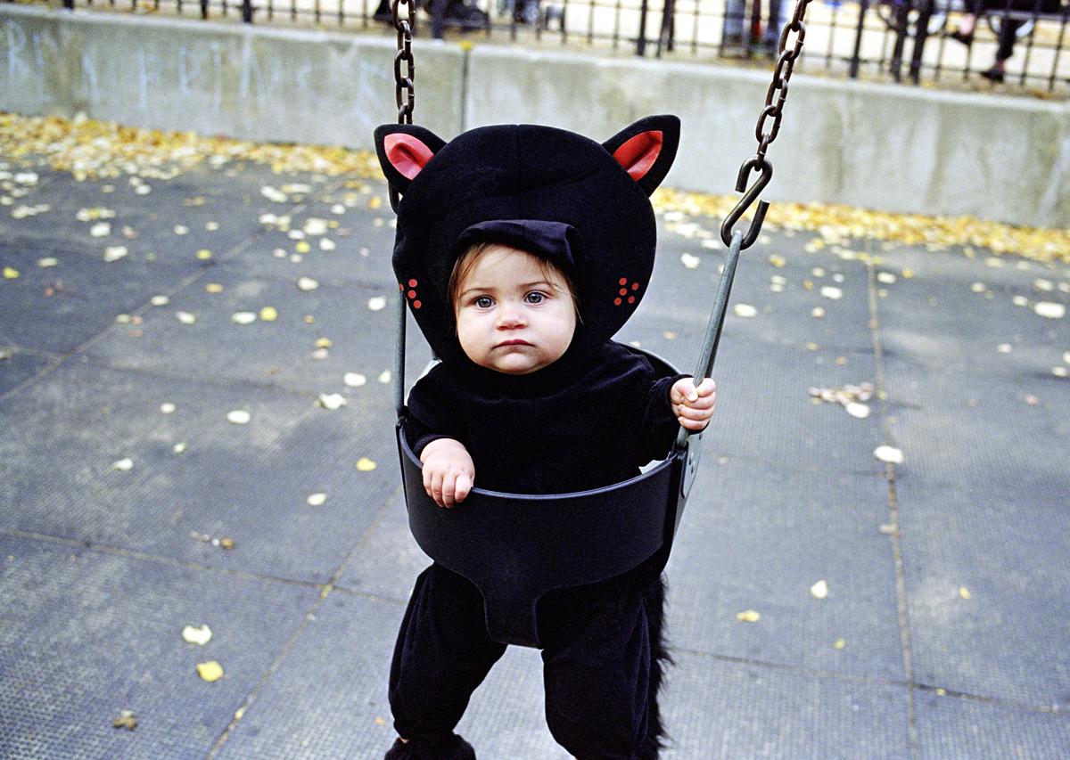 Baby in halloween costume on swing set
