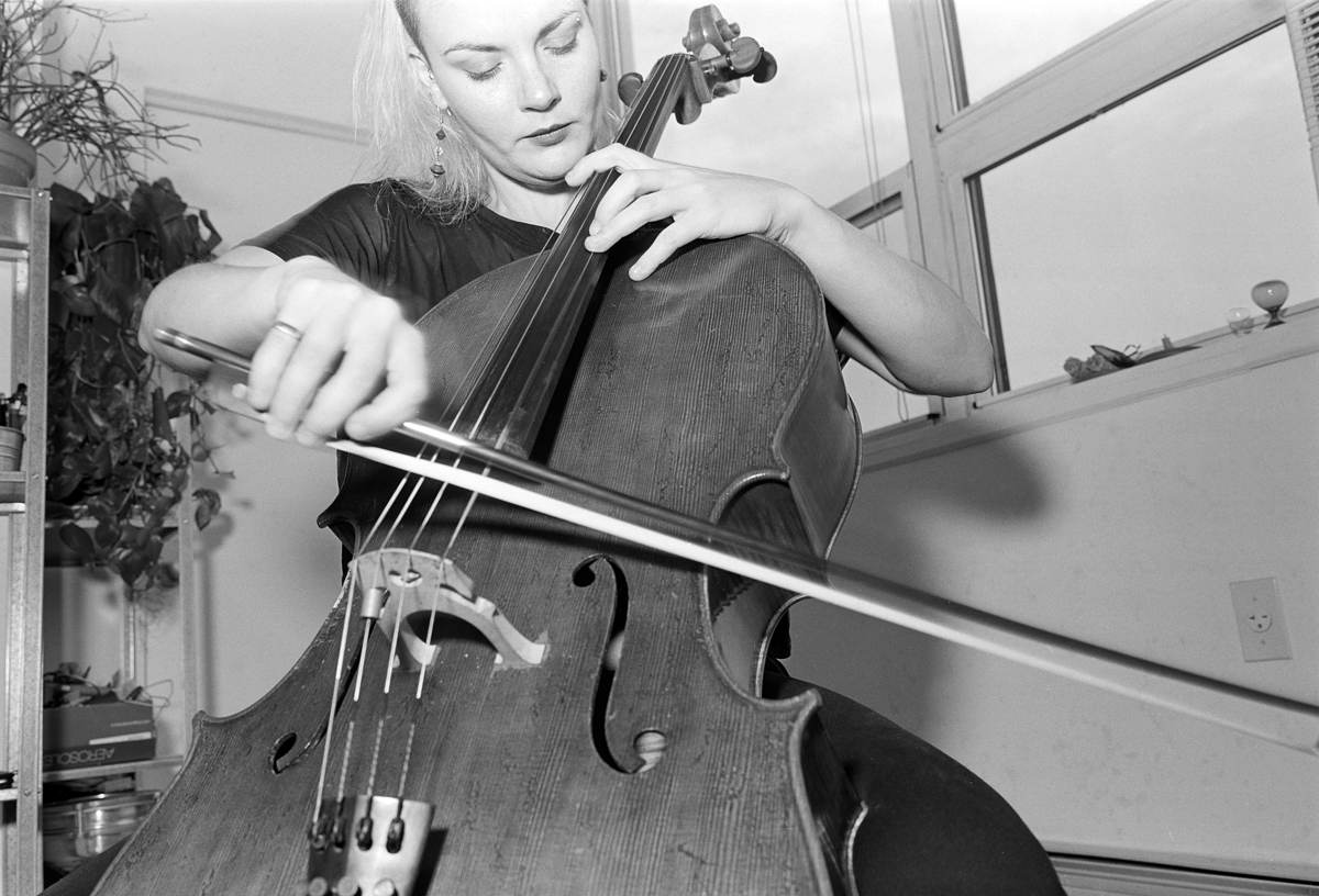 Brooklyn cellist practices in her apartment. Shot with kodak black and white film and a 6x9 medium format camera.