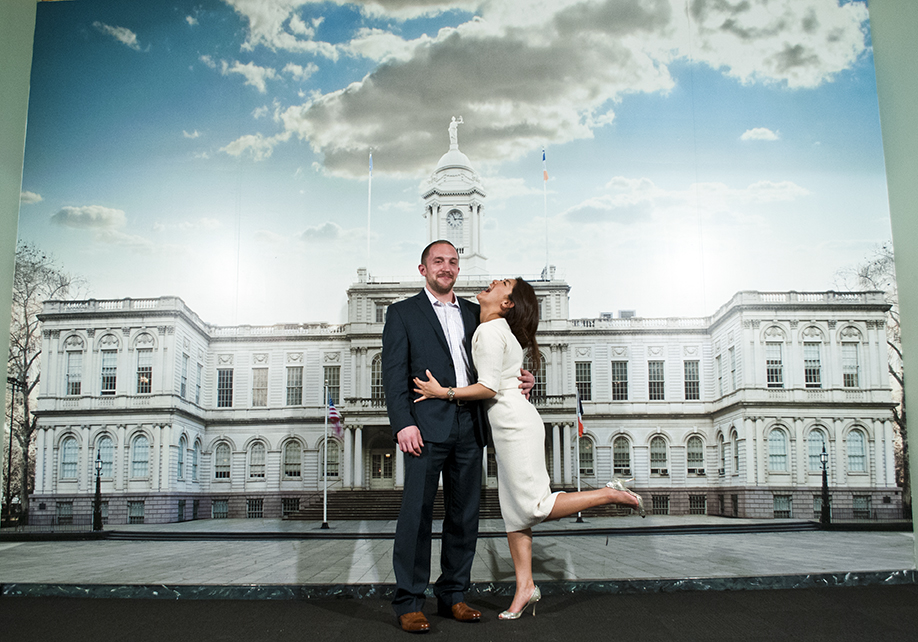 NYC CIty Hall wedding. Couple poses in front of City Hall poster. Shot with DSLR by Angela Cappetta.
