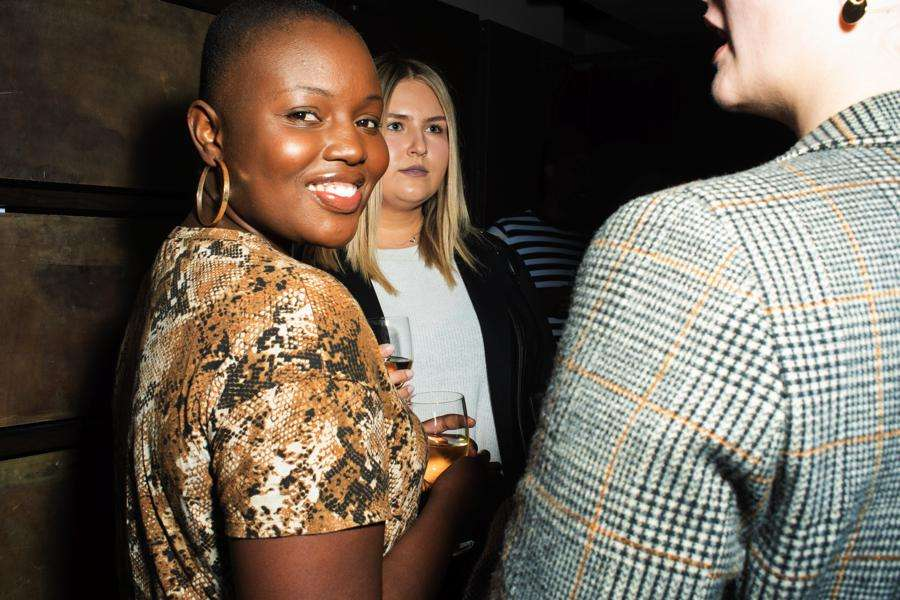 NYFW photography. Model with shaved head at a NYFW party smiles back at camera shot by fashion photographer Angela Cappetta with DSLR
