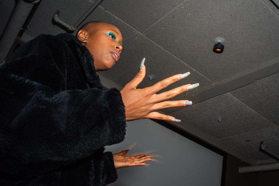 NYFW photography. Model in blue eye shadow and a shaved head speaks during a presentation at NYFW shot by fashion photographer Angela Cappetta.