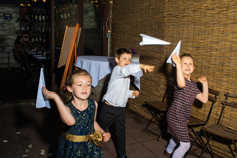 Children play with paper airplanes at a Brooklyn Bistro wedding shot by NYC Wedding photographer Angela Cappetta